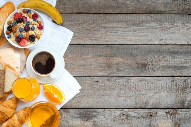 Healthy breakfast with fruits, berries, nuts, coffee, eggs, honey on wooden background