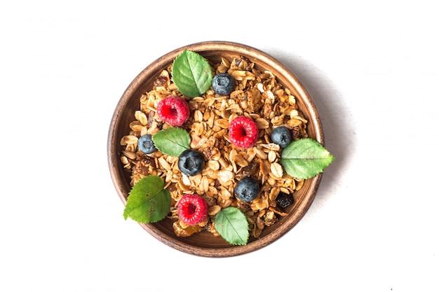 Здоровый завтрак с мюсли и ягодами на белом фоне Premium Фотографии