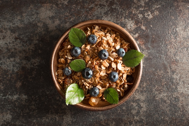 Healthy breakfast with granola and berries on dark background.