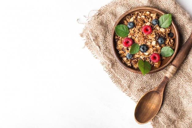 Healthy breakfast with granola and berries on white background