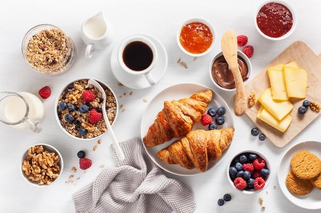 Здоровый завтрак с мюсли, ягодами, орехами, круассаном, джемом, шоколадной пастой и кофе. вид сверху