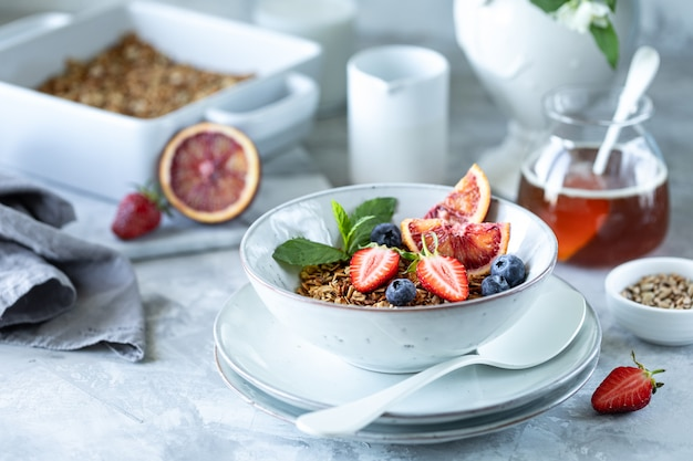 Healthy breakfast with granola, yogurt, fruits, berries on a white plate in white plate.