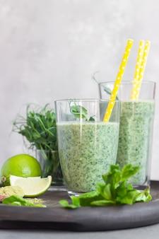 Здоровый завтрак с зеленым смузи с чайным порошком и ингредиентами на деревянном подносе