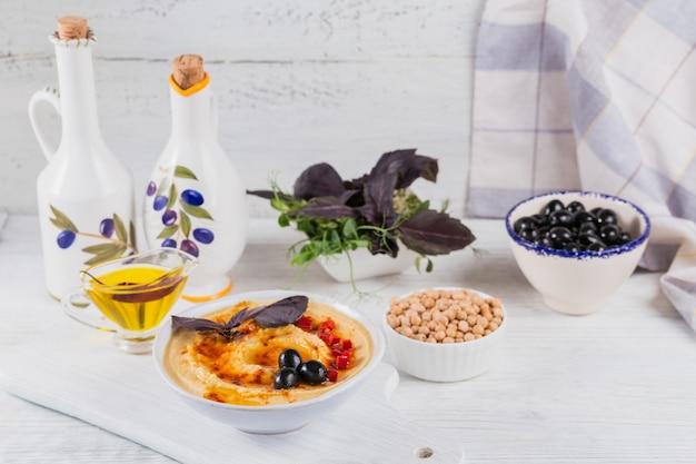 집에서 만든 후 머 스와 흰색 나무 표면에 블랙 올리브와 함께 건강 한 아침 식사. 다이어트와 건강한 간식.