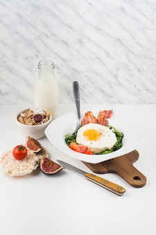 Healthy breakfast with milk bottle; cornflakes; fig and rice cracker against marble textured backdrop