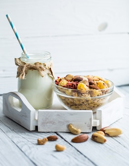 Healthy breakfast with milk in the jar and muesli with nuts