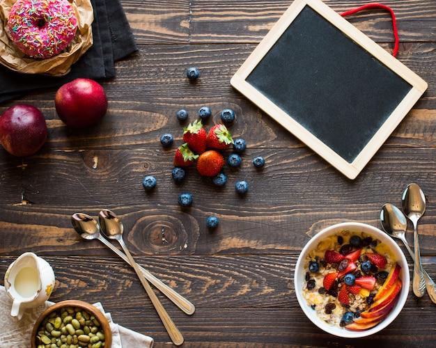 ミルク、ミューズリー、フルーツ、木製の背景に健康的な朝食。