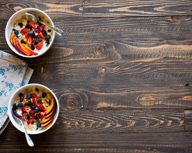 Healthy breakfast with milk,muesli and fruit, on a wooden background.