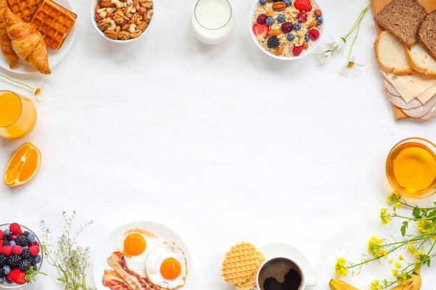 Healthy breakfast with muesli, fruits, berries, nuts, coffee, eggs, honey on white background