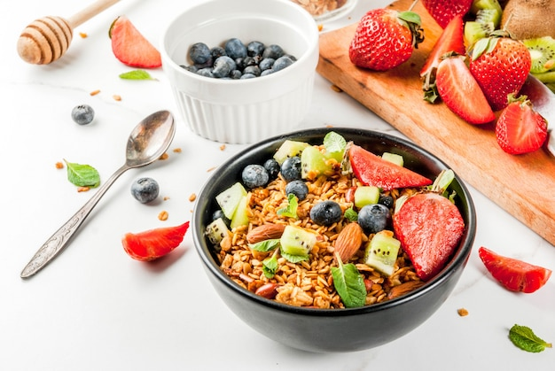 Healthy breakfast with muesli or granola with nuts and fresh berries and fruits  strawberry, blueberry, kiwi, on white table,