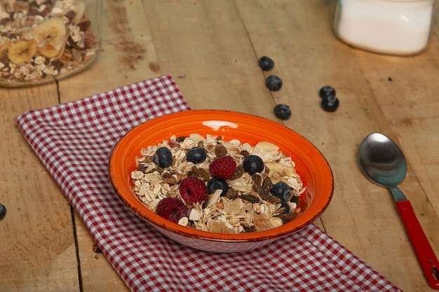 Healthy breakfast with oat flakes, nuts, blueberries and raspberries