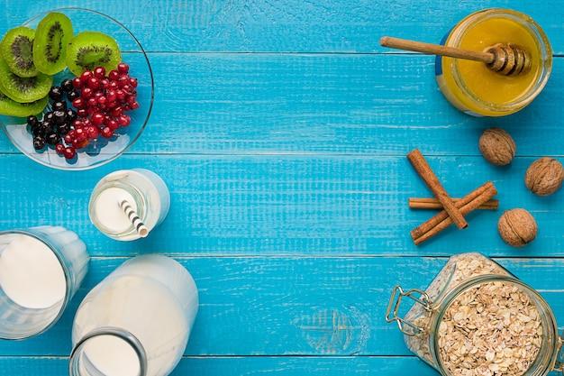 소박한 나무 배경에 오트밀 열매와 우유가 포함된 건강한 아침 식사