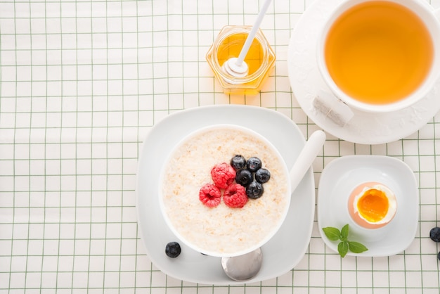 Healthy breakfast with oatmeal, egg and tea, copy space