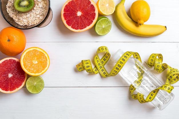 소박한 나무 테이블에 신선한 오트밀 과일과 물 한 병이 포함된 건강한 아침 식사
