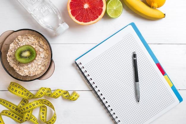 소박한 나무 테이블에 노트북과 함께 신선한 오트밀 과일과 물 한 병으로 구성된 건강한 아침 식사