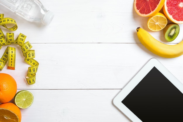 신선한 오트밀 과일과 물 한 병, 소박한 나무 테이블에 태블릿으로 구성된 건강한 아침 식사