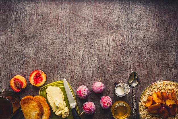 ガラスのボウルにオートミール、プラム、蜂蜜、クリーム、ダークウッドの背景に紅茶のカップで健康的な朝食。上面図。スペースをコピーします。静物。フラットレイ。トーン