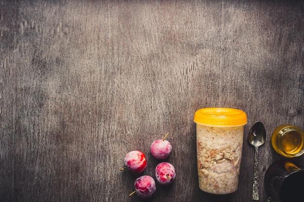 ダークウッドの背景に瓶、プラム、蜂蜜、紅茶のカップでオートミールと健康的な朝食。上面図。スペースをコピーします。静物。フラットレイ。トーン