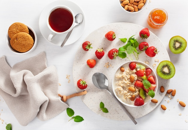 Healthy breakfast with oatmeal porridge, strawberry, nuts, jam and tea. top view