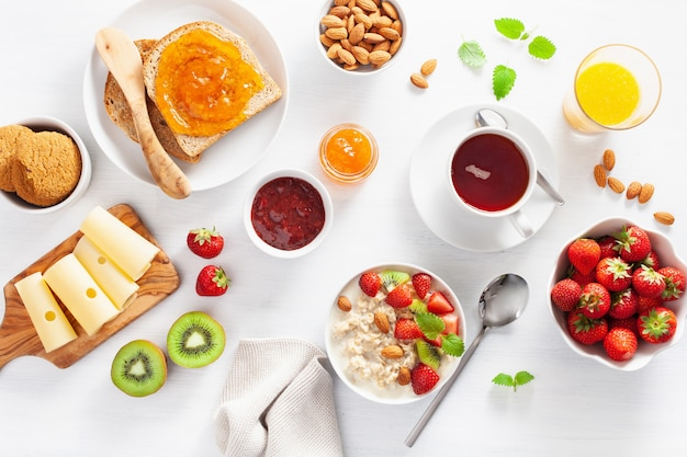 Healthy breakfast with oatmeal porridge, strawberry, nuts, toast, jam and tea. top view