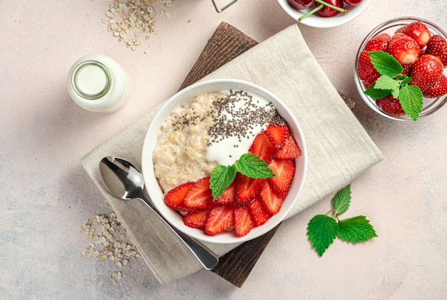 Healthy breakfast with oatmeal with strawberries and chia seeds on a pink background