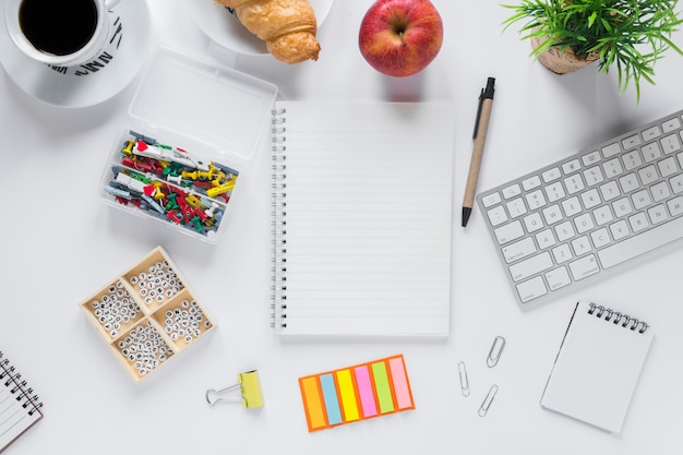 Healthy breakfast with office stationeries on white backdrop