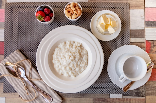 Healthy breakfast with rice porridge bowl with berries and nuts on the table