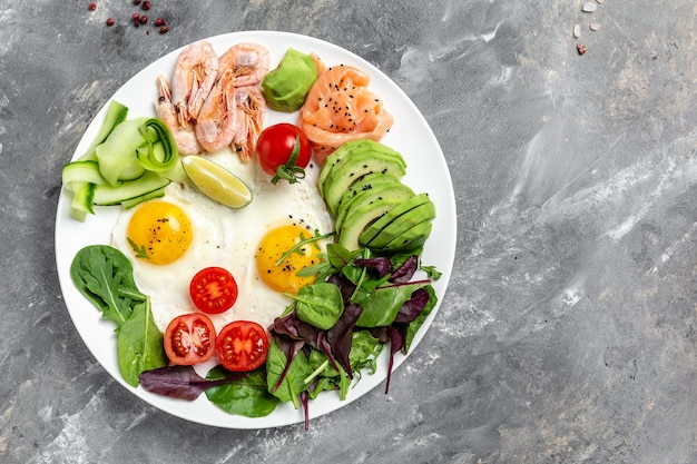 Здоровый завтрак с лососем, вареными креветками, креветками, яичницей, свежим салатом, помидорами, огурцами и авокадо. кето-диета. меню рецепт место для текста, вид сверху.