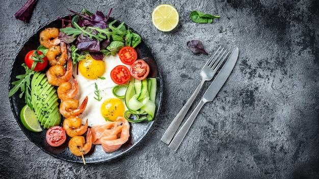 Здоровый завтрак с лососем, креветками на гриле, креветками, яичницей, свежим салатом, помидорами, огурцами и авокадо. кето-диета. вид сверху.