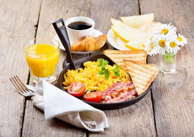 木製のテーブルにスクランブルエッグ、ジュース、フルーツと健康的な朝食