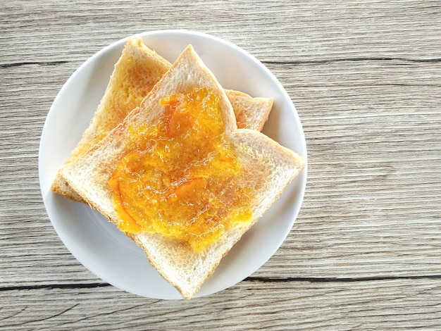 Healthy breakfast with tasty breakfast toasts (with orange and pineapple jam) on wooden table.