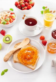 Healthy breakfast with toast, porridge, strawberry, nuts, jam and tea