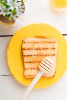トーストしたパンと白い背景の上に花と花瓶の近くの蜂蜜と健康的な朝食。黄色のトーン。上面図。