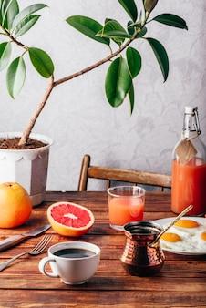 トルココーヒー、目玉焼き、ジュース、フルーツを使ったヘルシーな朝食