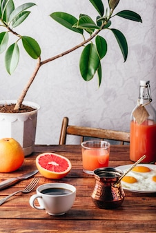 Healthy breakfast with turkish coffee, fried eggs, juice and fruits