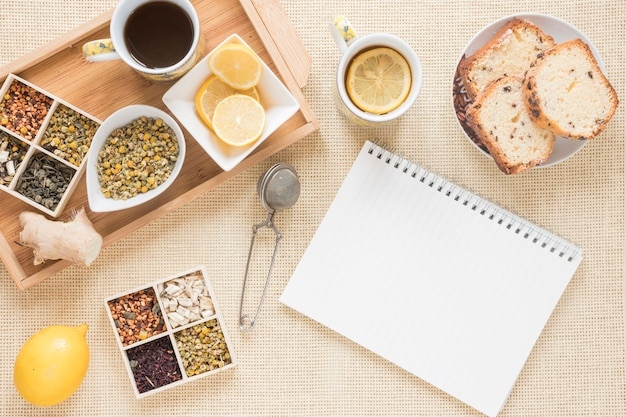 Healthy breakfast with variety of herbs; lemon; strainer; bread; ginger and blank spiral notepad