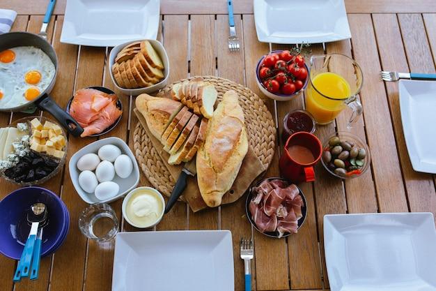 健康的な朝食朝食にジュースを注ぐ家族はおいしい食べ物を食べています夏