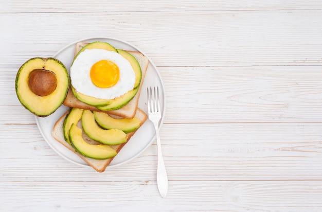 白い木製の背景にアボカドと健康的な朝食トーストフラットレイ
