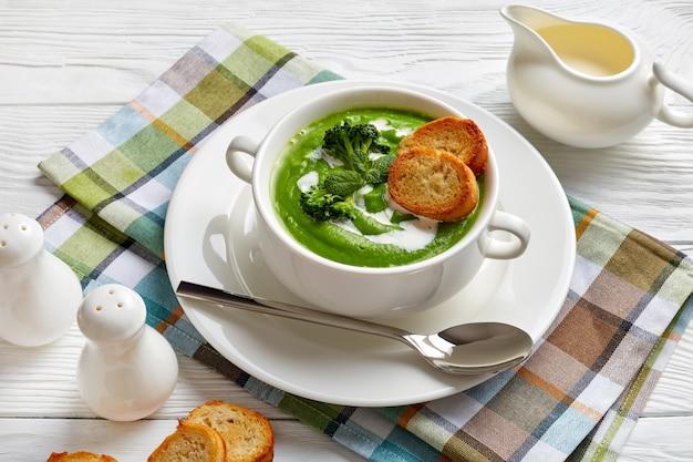 トーストしたバゲットと生クリームのスライスを添えた白いスープボウルに入ったヘルシーなブロッコリークリームスープ、上からの眺め、クローズアップ