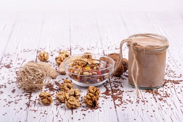 Здоровый коричневый коктейль с грецким орехом и засахаренные фрукты лежат на столе