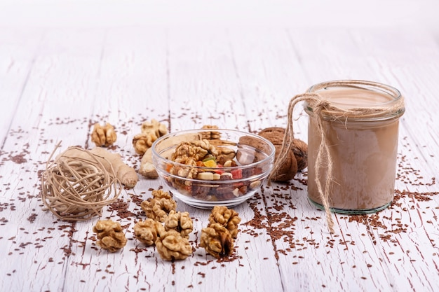 Healthy brown smoothie with walnut and candied fruits lie on the table