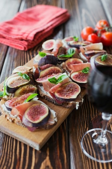 Healthy bruschettas with bread, cream cheese, prosciutto, figs and basil on rustic wooden table