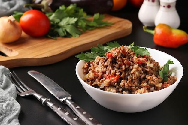 Полезная гречка, приготовленная с овощами в белой миске на темноте