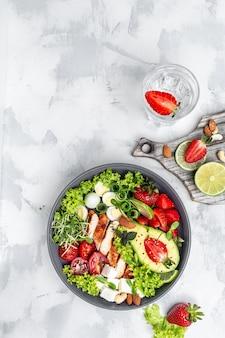 Здоровый обед в чаше будды с жареным цыпленком и авокадо, сыром фета, перепелиными яйцами, клубникой, орехами и листьями салата. вкусная концепция сбалансированного питания. вертикальное изображение. вид сверху. место для текста.