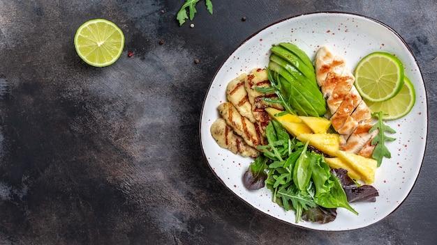 구운 닭고기, 할루미, 아보카도, 그린 로켓 샐러드, 라임이 포함된 건강한 부처 그릇
