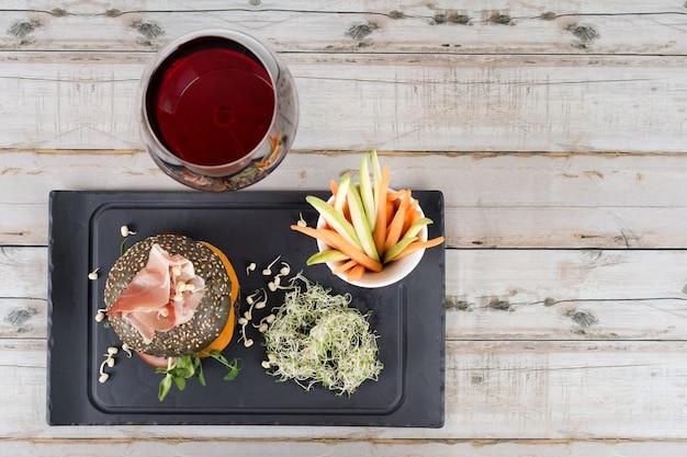 Полезный бургер с хамоном, помидорами, зеленью и черными цельнозерновыми булочками, овощными палочками и красным вином на черной грифельной доске