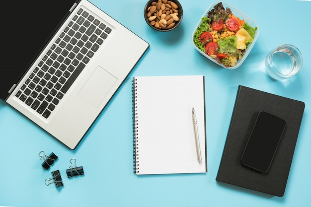 Здоровый бизнес-ланч в офисе, салат, миндаль, вода на синем. Premium Фотографии