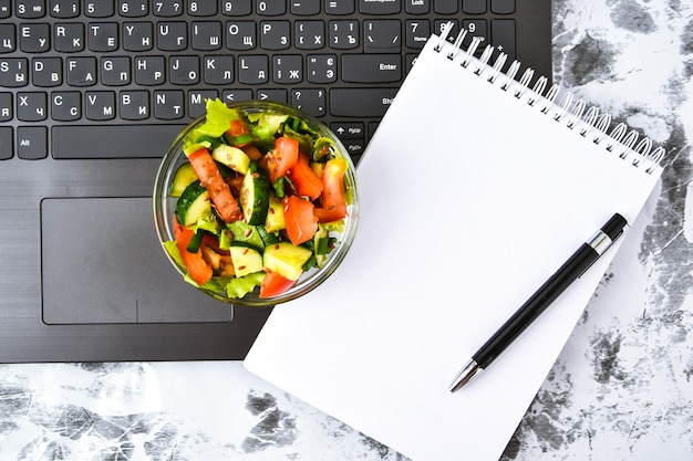 Healthy business lunch snack in office with vegetable salad, empty notebook and pen