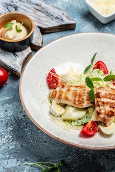 Healthy caesar salad with grilled chicken, cheese and croutons, quail eggs and cherry tomatoes, delicious balanced food concept, vertical image. top view. place for text.