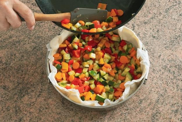 Здоровый торт из овощей. небольшие кусочки овощей приготовлены и готовы к запеканию в тесте. красочно и вкусно